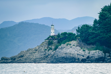 Light house in Busan on the beach South Korea. This view was captured much further up the beach using a zoom lense to capture more of the landscape