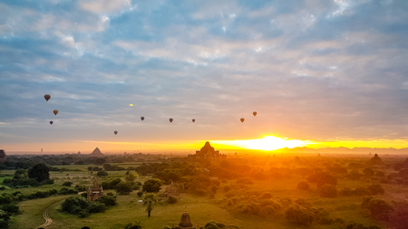 Balloons over the fields and temples of Bagan Burma Myanmar. One of the most magical sights you will see as the sun rises over this amazing landscape Stock Photo