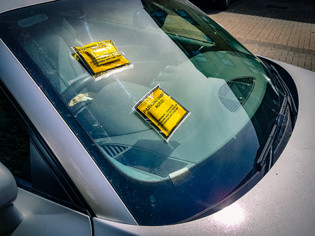 Shot of car with two parking tickets issued on windscreen parking fine