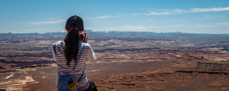 Tourists talking and posing for photos at the Canyonlands National Park Utah USA