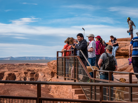 Holiday makers visiting and taking photos of the famous horseshoe bend near Page Arizona Grand Canyon