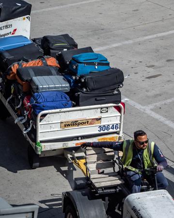 Baggage Handler driving baggage truck for loading and unloading passengers bags at Las Vegas McCarren Airport