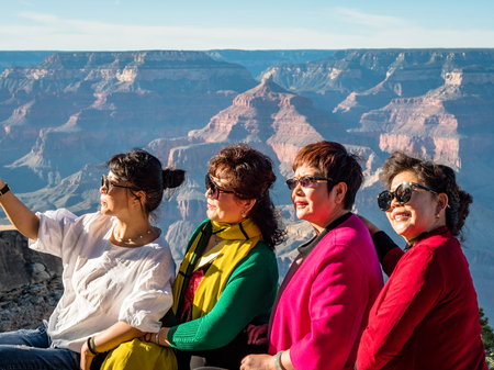 Elderly group of Asian women tourists posing for photos at the Grand Canyon South Side Arizona Фото со стока - 122971855
