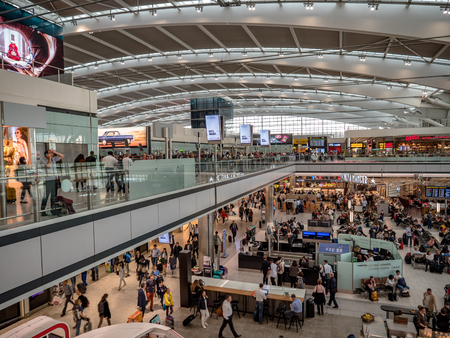 London Heathrow Airport terminal 5 departure hall restaurants, shops and cafes. Passengers waiting to board flights