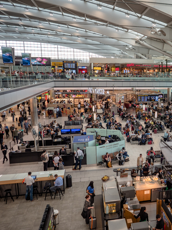 Portrait London Heathrow Airport terminal 5 departure hall restaurants, shops and cafes. Passengers waiting to board flights Редакционное