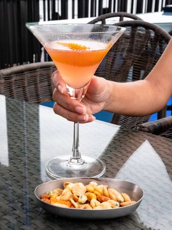 Pattaya, Thailand - August 1, 2019: Gorgeous chilled fruity cocktail and side snacks on roof top bar in thailand Stockfoto - 128781094