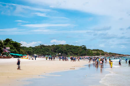 Groups of Chinese holiday makers on the beach getting on speedboats on the island of Koh Samet thailand