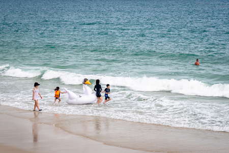 Chinese family taking inflatable toy into the sea to play and have fun on the island of Koh Samet Thailand