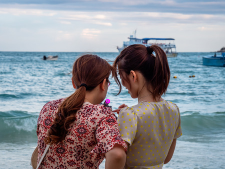 Chinese Tourists posing for photos and selfies on the Thai Island of Koh Samet Thailand