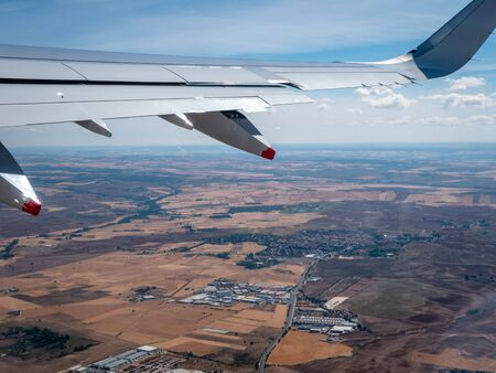 Shot of aircraft wing and Madrid Spanish countryside during take off from Madrid Airport