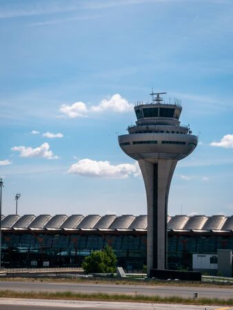 View of Madrid-Barajas Adolfo Suárez Airport Satellite Terminal and air traffic control tower in Madrid Spain. Multiple Iberia planes lined up waiting at terminal