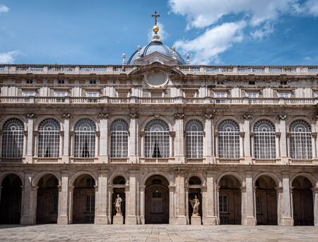 Architecture shot of the Royal Palace of Madrid Inner courtyard plaza. No People. Must visit tourist attraction in Madrid. Shot in Summer with sparse clouds and blue skies. Palacio Real de Madrid Royalty High Society.