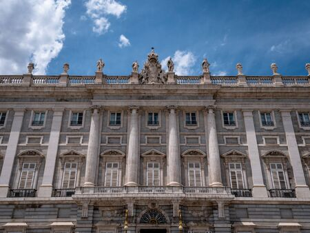 View of Royal Palace of Madrid Front Entrance and Facade. Tourists taking photos and selfies in the plaza outside. Shot in Summer with sparse clouds and blue skies. Palacio Real de Madrid a top city attraction and must visit place in Madrid.