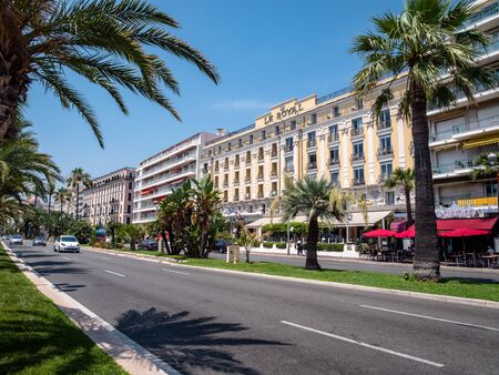 Nice stone beach and promenade with turquoise calm water of cote d'azur. Promenade des Anglais. tourists, sunbeds and umbrellas on summer hot day
