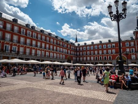 Tourists exploring the famous Plaza Major in Madrid. Taking photos and dining at the squares many outside fine dining restaurants. Top tourists attraction.