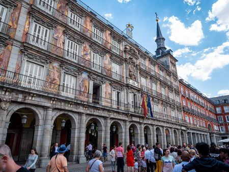 View of Casa de la Panadería Front Entrance and Facade in Plaza Major Madrid. A municipal building from 1619 with a frescoed facade, repainted in 1992 by artist Carlos Franco. Shot in Summer with sparse clouds and blue skies. A top city attraction and mu