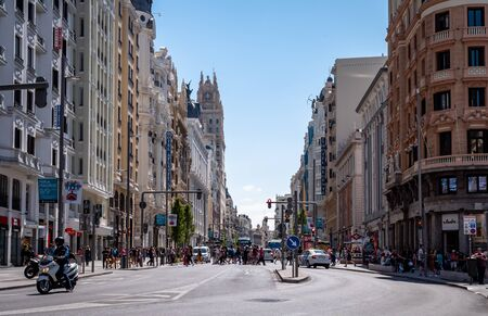 View down the famous Calle Gran Vía street in Madrid. Shops, retail, restaurants, cafes and bars line the street as locals and tourists go about their daily business. Scene shows city life on a summers sunny day.