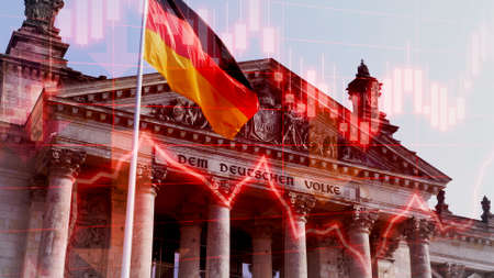 Concept Piece to show the German economy in decline as it struggles to cope with the COVID19 Economic crisis. Showing Reichstag building with German flag with negative chart data and performance