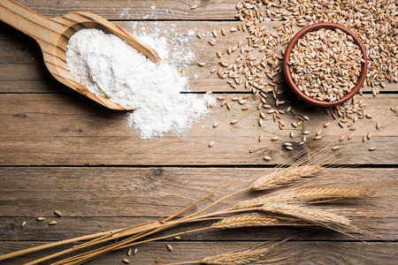 grains de l'oreille, la farine et wholegrains sur table en bois