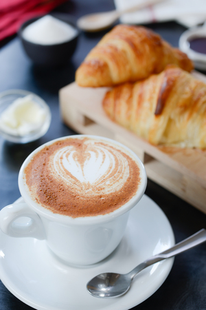 Cappuccino decorato e croissant