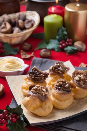 crema: Bigne alla crema di castagne con fichi e noci su sfondo natalizio