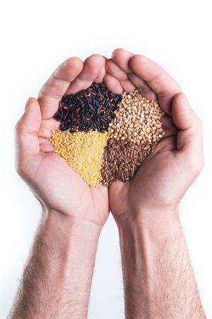 Man's hands holds gluten free coloured seeds and cereal