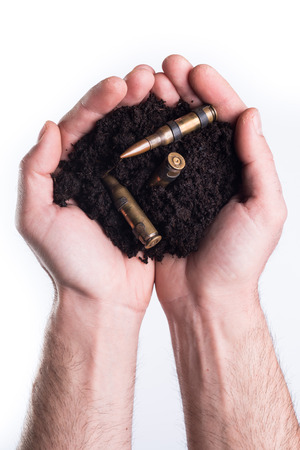 topsoil: Mans hands holds topsoil with bullets on white background