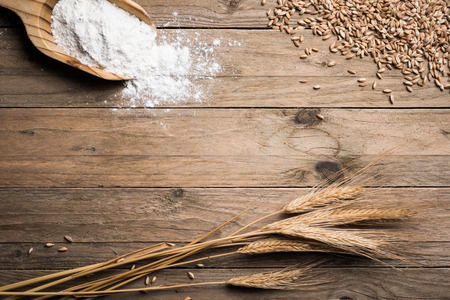 Ear grains, flour and wholegrains on wood table Archivio Fotografico
