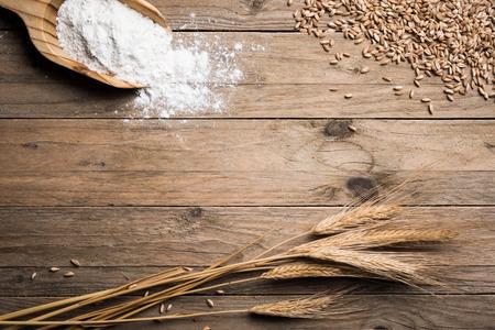 Ear grains, flour and wholegrains on wood table Stock Photo