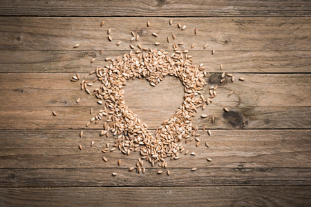hulled: Heart shape wheat on wood table Stock Photo