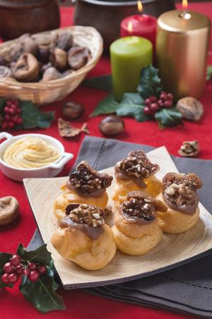 bigne: Bigne alla crema di castagne con fichi e noci su sfondo natalizio