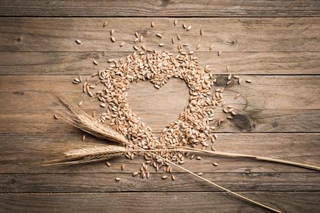 Heart shape wheat on wood table Archivio Fotografico