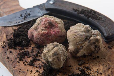 Alba white truffle tuber on wood board and truffle's knife