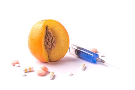 OGM orange fruit with pills and syringe