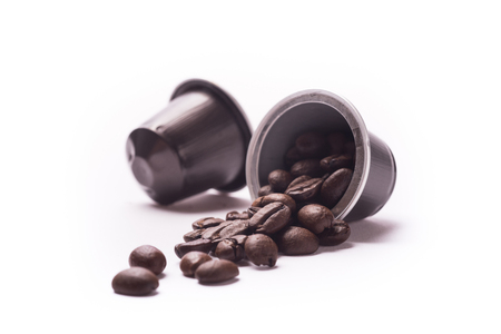 Toasted coffee beans spill out from a capsule on white background