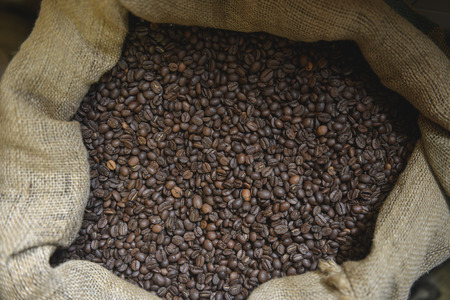toasted coffee beans on a juta textile bag composition