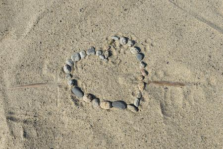 stones heart shape on a beach sand by the sea