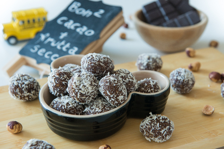 sweet dates chocolate balls with coconuts on colorful still life food composition