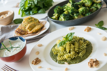 complete vegan lungh with pesto fusilli, courgette pancakes, yogurt cream and spinach Stock Photo