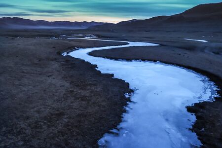 Frozen river in a north mongolian steppe grassland