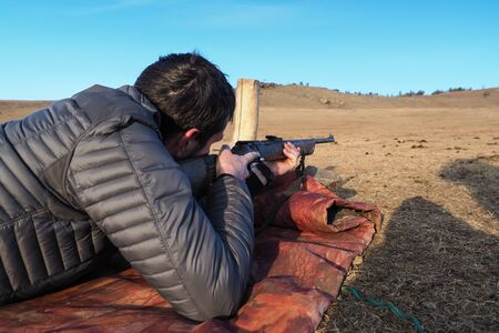 Shoother hands a old rifle in mongolian steppe desert