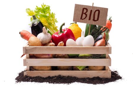 Organic vegetables in wooden rustic box and topsoil with cardboard square tag. Price tag, gift tag, sale tag, label isolated on white background Archivio Fotografico