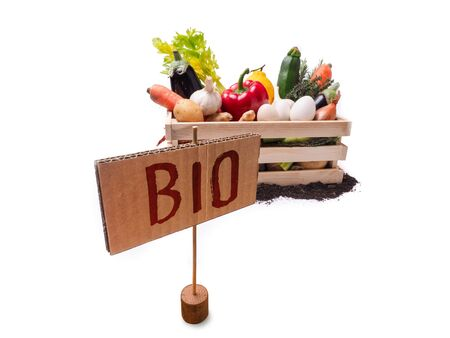 Organic vegetables in wooden rustic box and topsoil with cardboard square tag. Price tag, gift tag, sale tag,  label isolated on white background