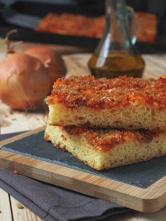 Sicilian italian traditiona pizza focaccia bread called sfincione, preppared with onions, tomato sauce, anchovies, caciocavallo cheese and bread crumbs