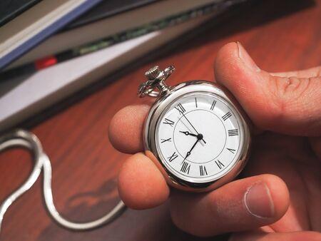 caucasic man holding a pocket clock on classic desk background