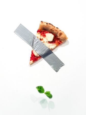 SPizza slice taped on the wall with duct tape reminding the composition of Maurizio Cattelan Archivio Fotografico