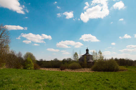 Pleasant sunny summer landscape: old blue sky and clouds, green grass and old historical Slavic Orthodox country church building . A happy idyllic scenery view. Good weather.