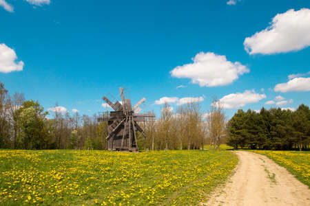 Old ancient historical windmill in countryside village. Pleasant sunny weather, blue sky, white clouds, green trees and scenery view.
