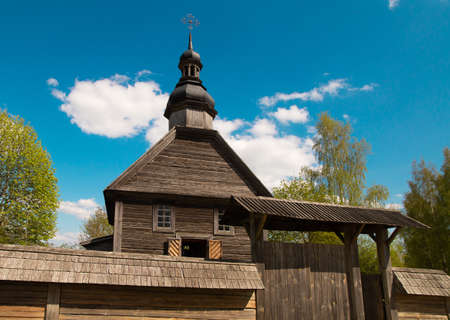 Pleasant sunny summer landscape: old blue sky and clouds, green trees and old historical Slavic Orthodox country church building . A happy idyllic scenery view.