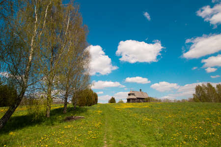 Pleasant sunny summer landscape: old blue sky and clouds, green grass, yellow dandelion flowers on a meadow and old historical Slavic Orthodox country church building . A happy idyllic scenery view.